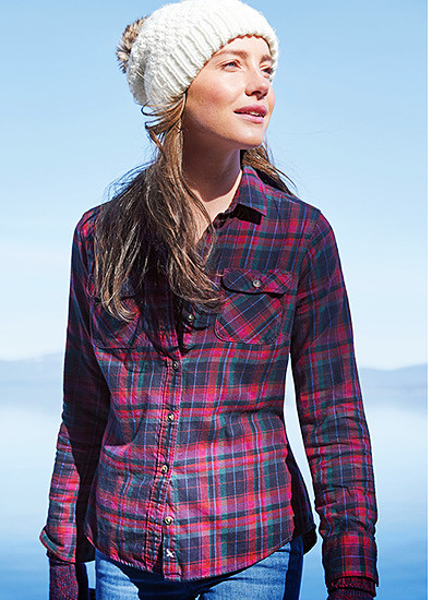 A women wearing a plaid flannel shirt stands by a lake