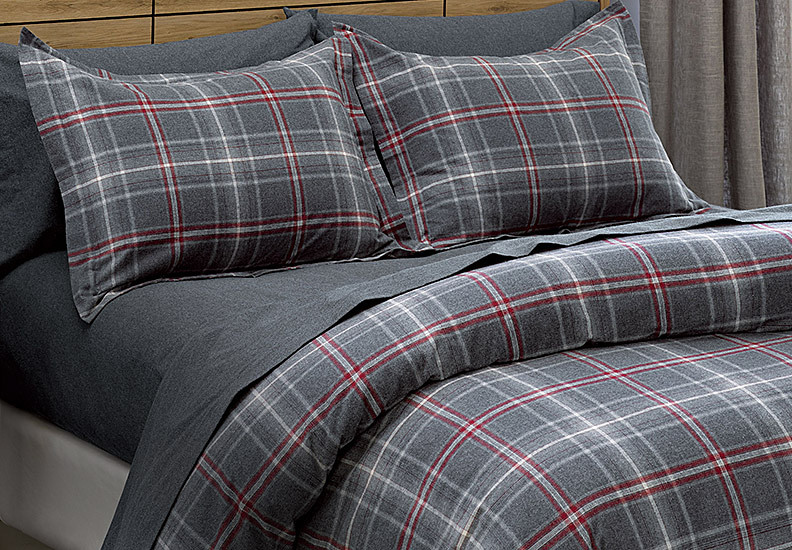A bed made up with flannel sheets