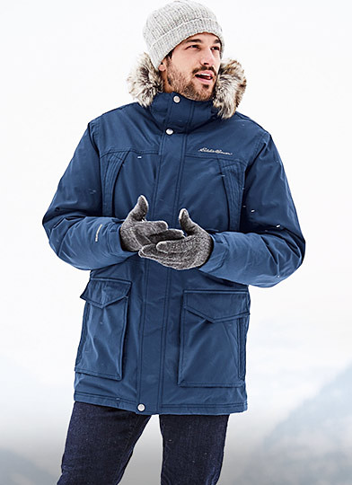 A man wearing a Superior Down Parka walks in a winter landscape