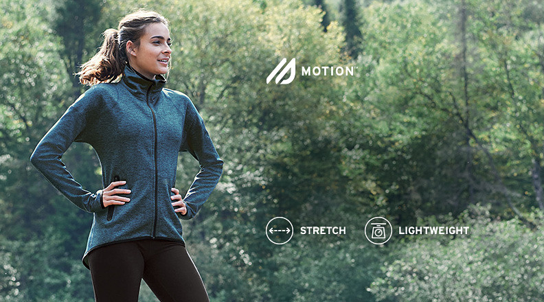 A woman wearing an After Burn 2.0 Jacket stands in the woods