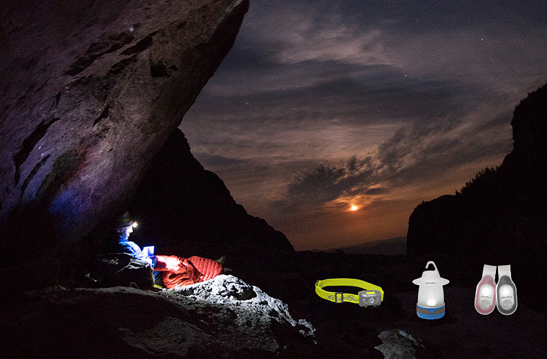 Mountainside photo of a climber in his bivy using a headlamp.