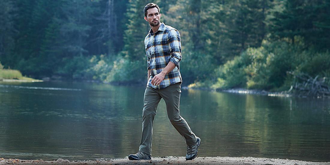 A man wearing Horizon Guide Pants hikes near a river