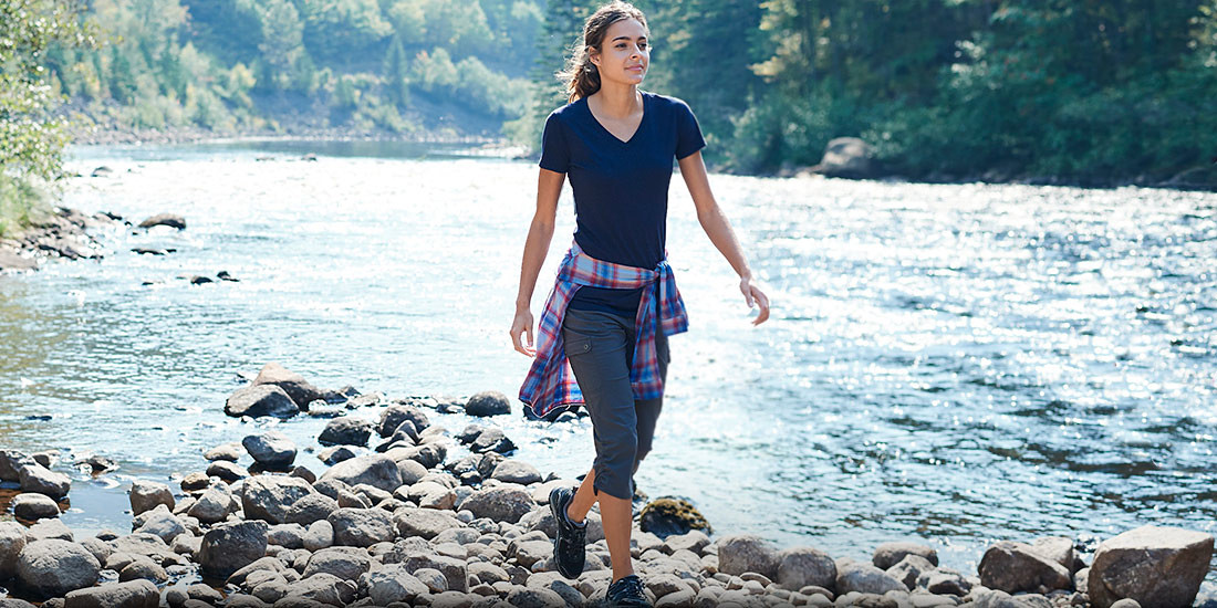 A woman wearing Horizon Capris hikes near a river