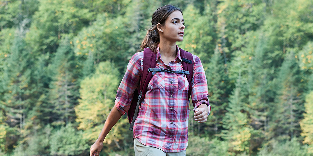 A woman wearing a mountain shirt hikes in forest