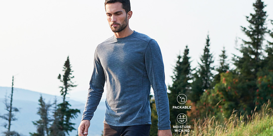 A man wearing a Contour Long-Sleeve Crew hikes in the hills