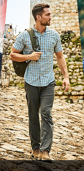 A man in Horizon Guide pants walks on a cobblestone street.