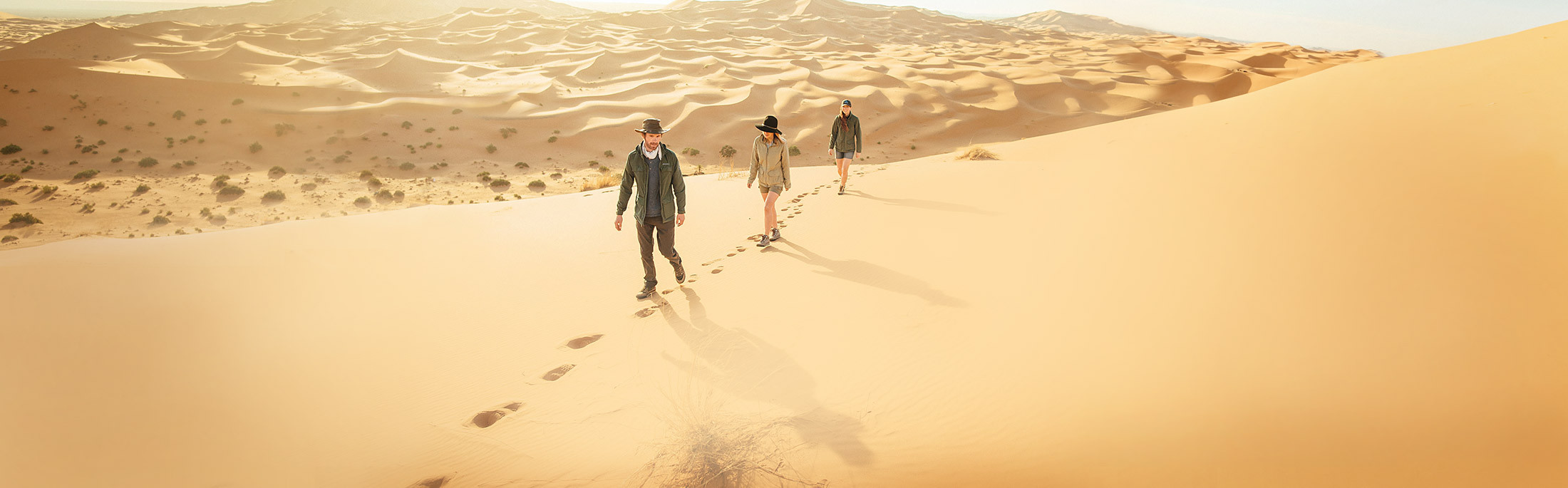 Three travelers walking across sand dunes in Morocco