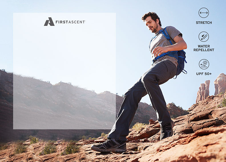A man wearing Guide Pro pants hikes down a hill