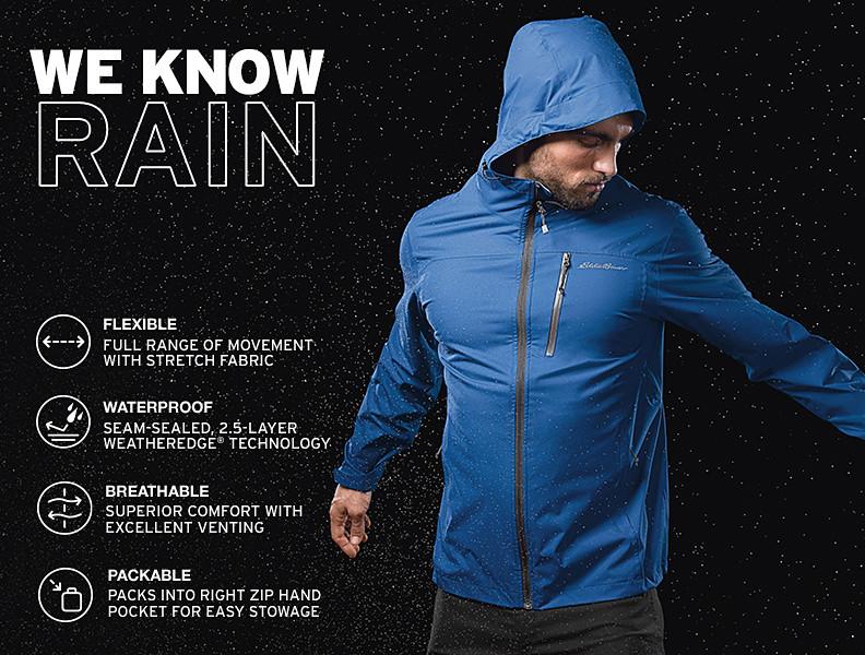A man wearing a Cloud Cap Stretch Jacket stands in the rain