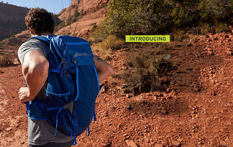 A man wearing an Adventurer Trail Pack hikes in the desert