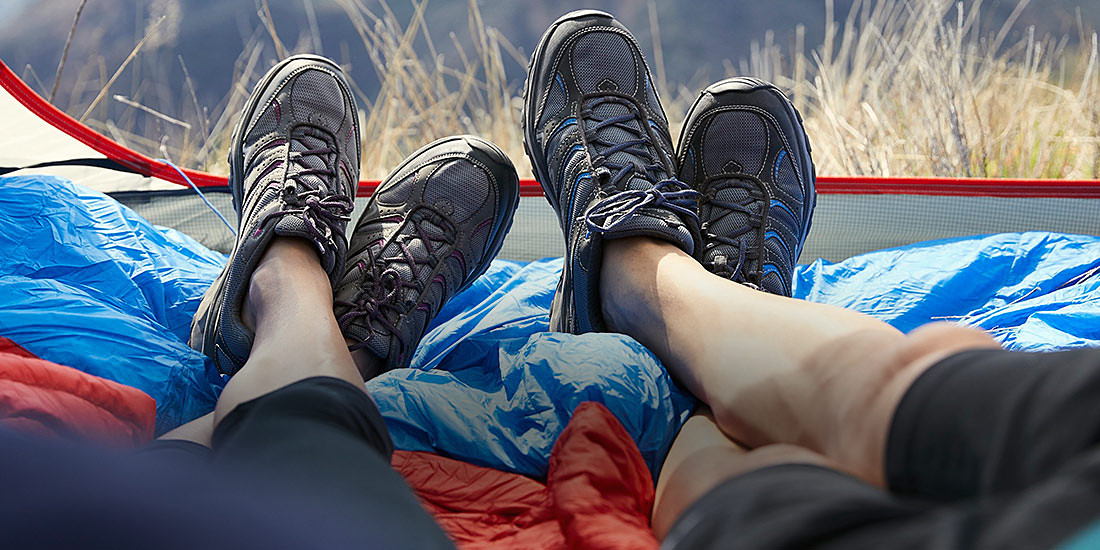 Two hikers wearing Lukla Pros recline in a tent