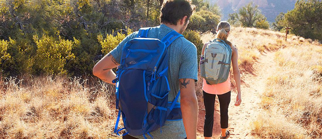 Two hikers wearing backpacks hike in the desert