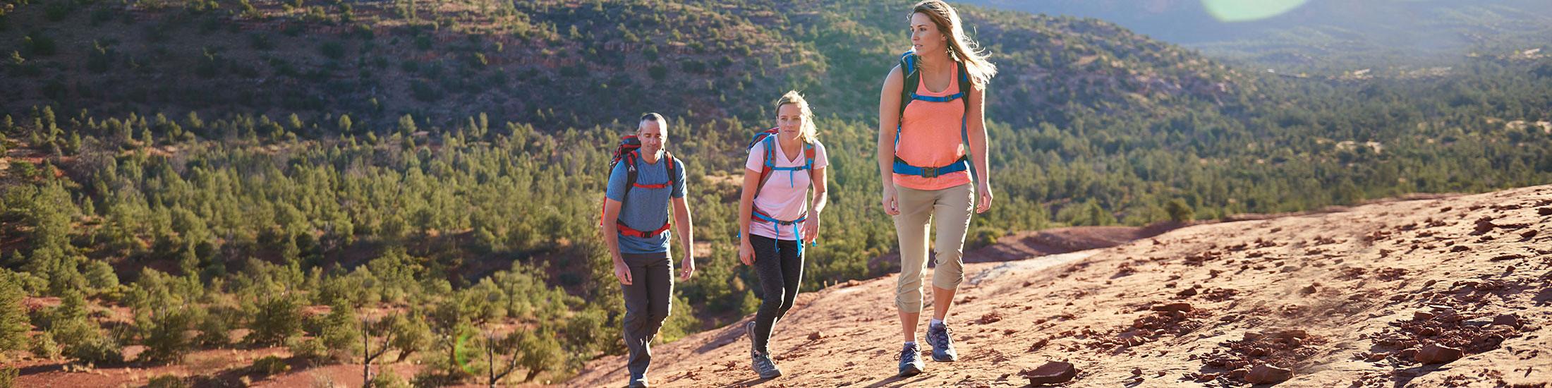 Three people hike up a hill in Sedona, AZ