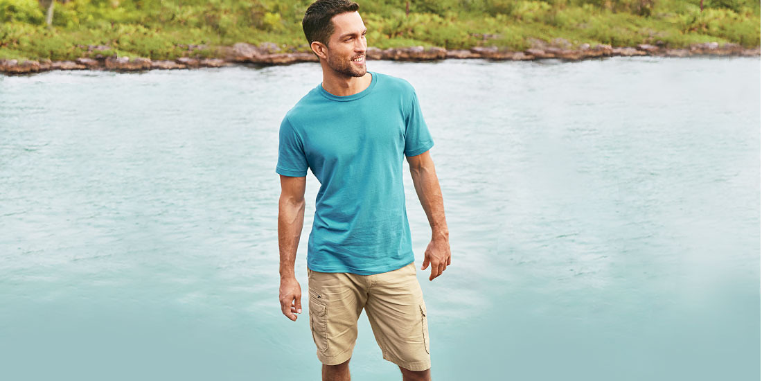 A man wearing Legend Wash T-shirt stands on the beach
