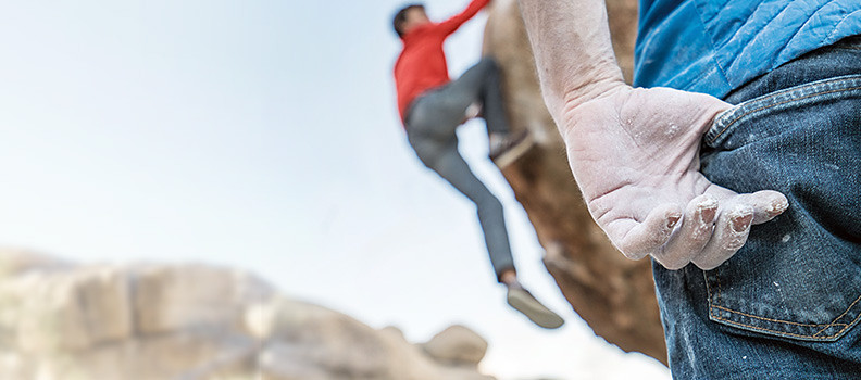 Image of a man rock climbing in Flex jeans