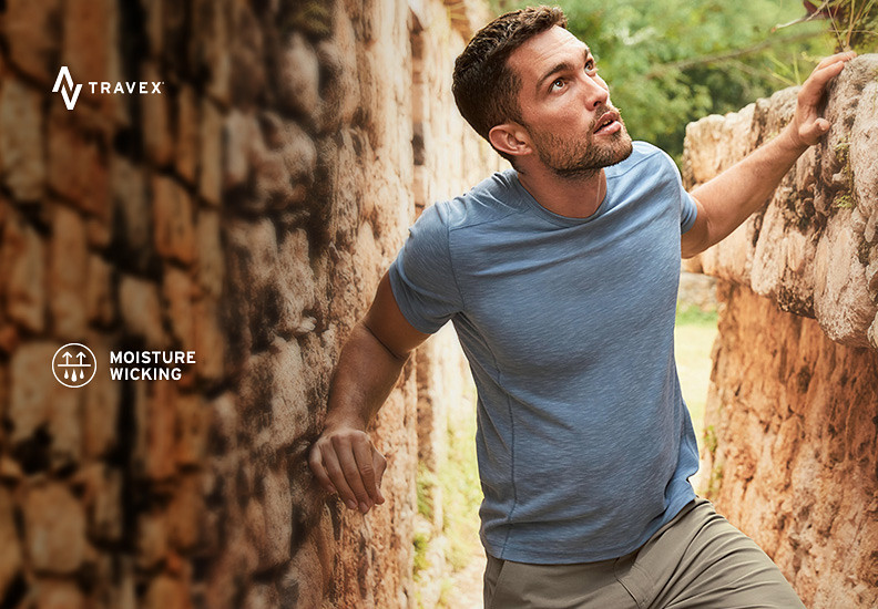 A man wearing a contour t-shirt explores ancient ruins