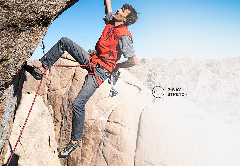A man rock climbing in flex jeans