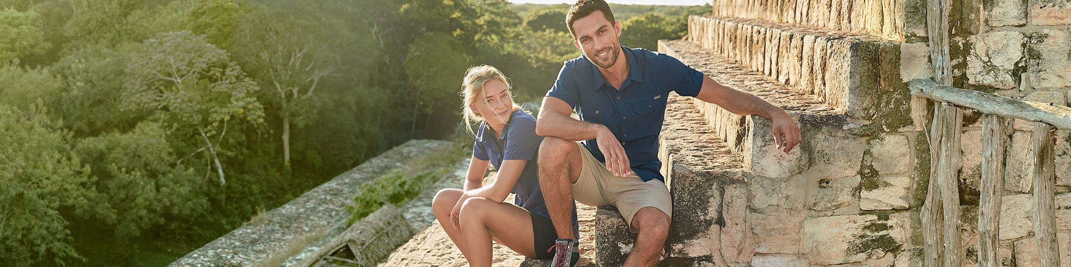 A man and a woman wearing Departure Shirts and Horizon Shorts explore ancient ruins in an exotic location