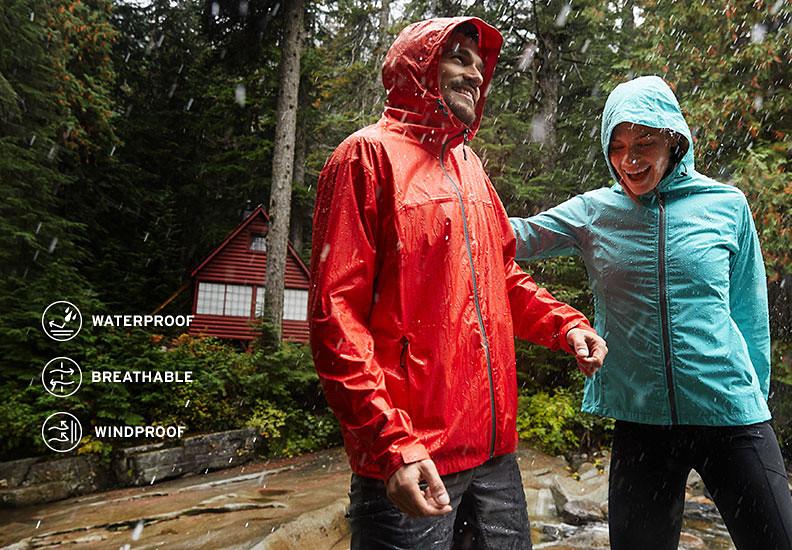 Two people in rain jacket walk in the woods