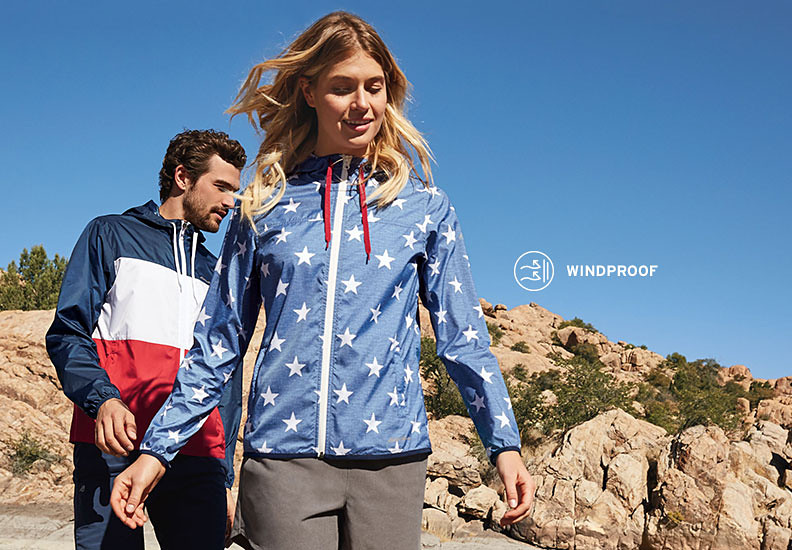 A man and a woman hiking in Momentum Light Jackets