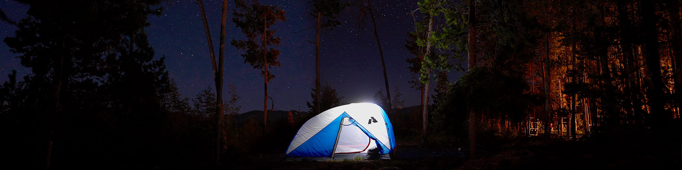 An illuminated Stargazer 2 Person Tent in the woods