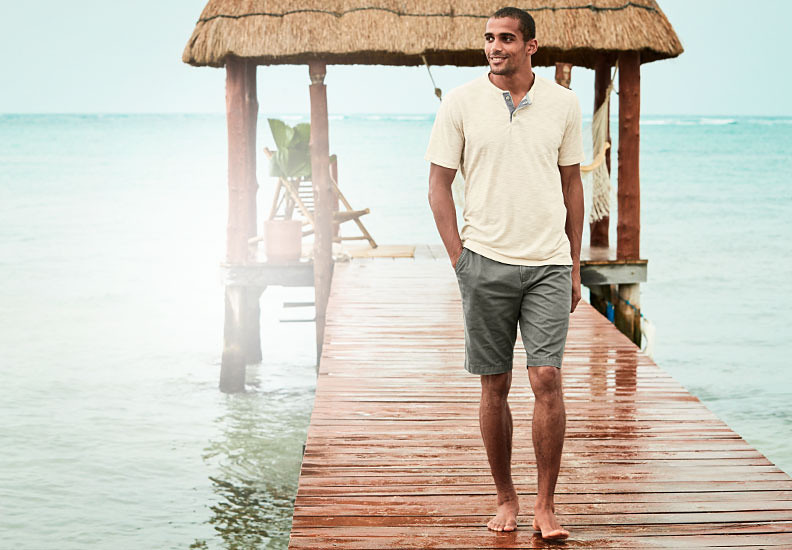 A man wearing Legend Wash shorts walks on a dock