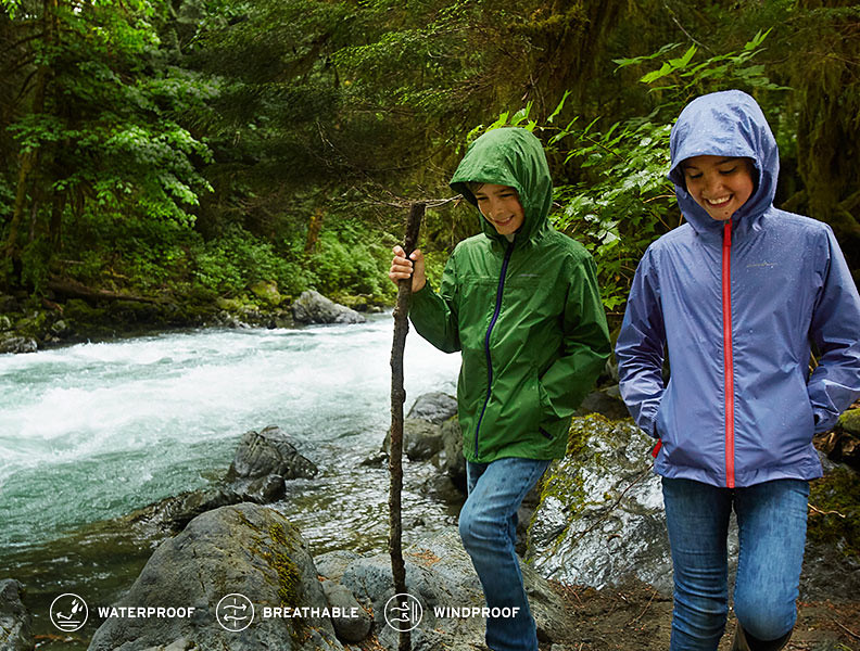 Two kids wearing Cloud Cap Rain Jacket hike by a river in the rain