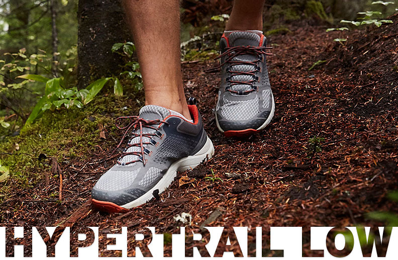 Close up shot of a man's feet wearing Hypertrail Low shoes walking on a trail in the woods