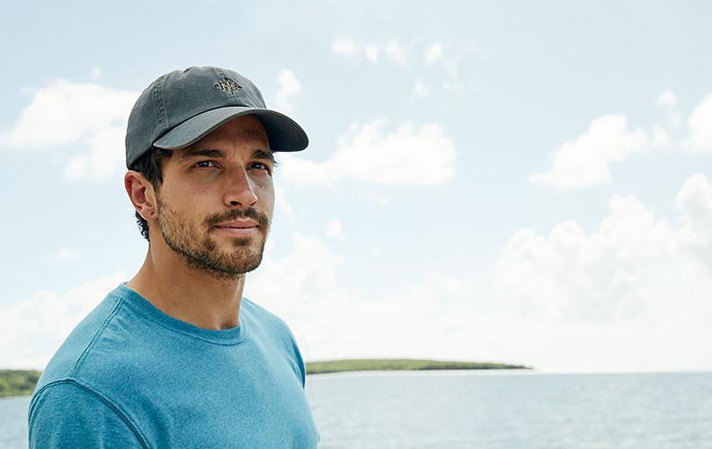 A man wearing a baseball cap stands on a beach