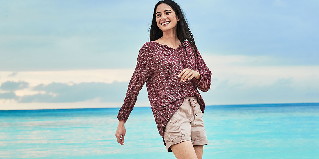 A woman wearing a Thistle Top and Kick Back Twill Shorts walks on the beach