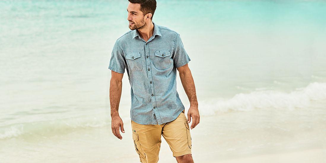 A man wearing a Vashon Shirt and Versatrex Cargo Shorts walks on the beach