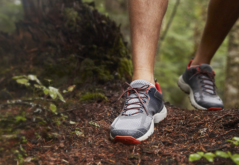 A close up image of a man wearing Hypertrail Low shoes walking on a trail in the woods
