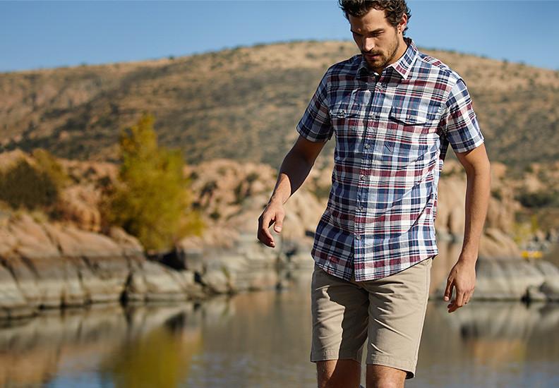 A man wearing Legend Wash shorts walks beside a river