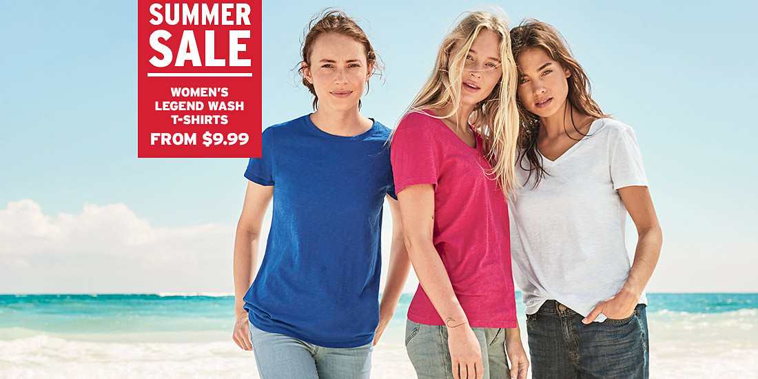 Three women wearing Legend Wash T-shirts stand on the beach
