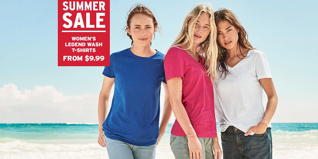 Three women wearing Legend Wash T-shirts stand on the beach
