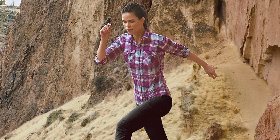 A woman wearing a Mountain Shirt hikes in the desert