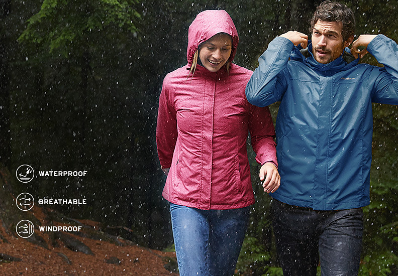 A man and a woman wearing Packable Rainfoil Jackets walk in the rain