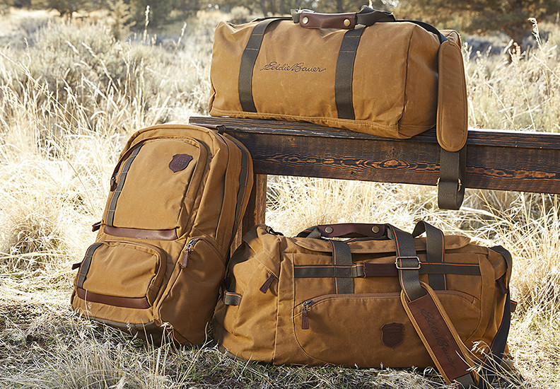 Two duffels and a backpack propped against a wooden bench in a field of golden grasses.