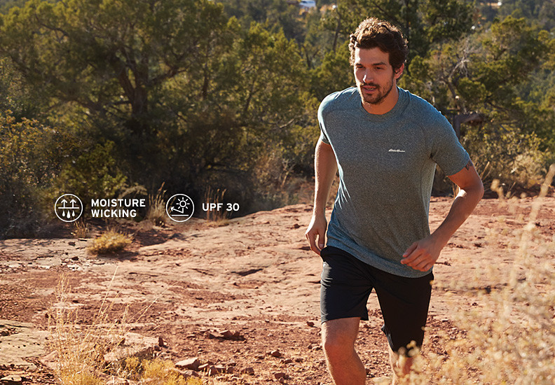 A man wearing a Resolution T-shirt and Knit shirt runs up a hill