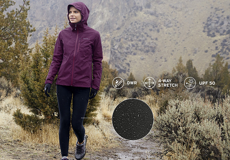 A woman wearing DWR Trail Tights hikes up a hill