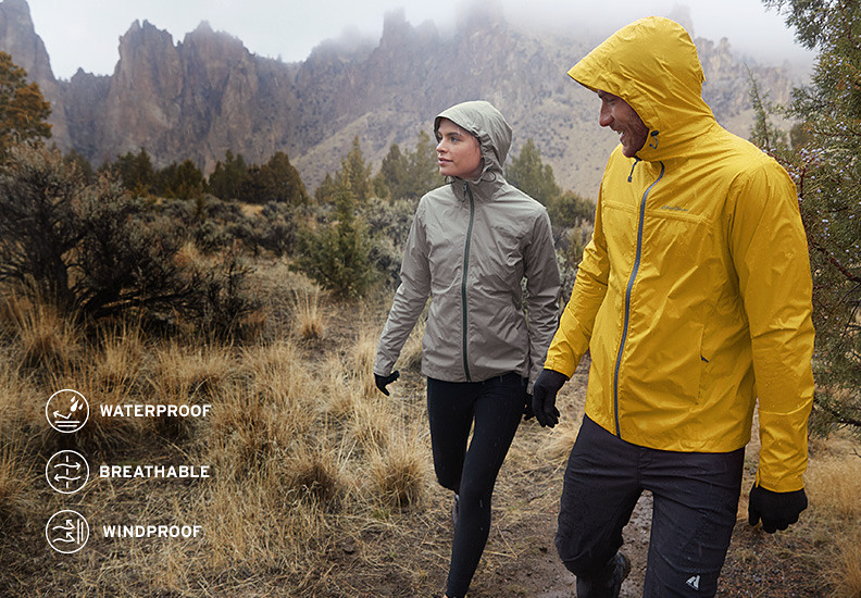 Two people in rain jackets walk on grassy mountain trail