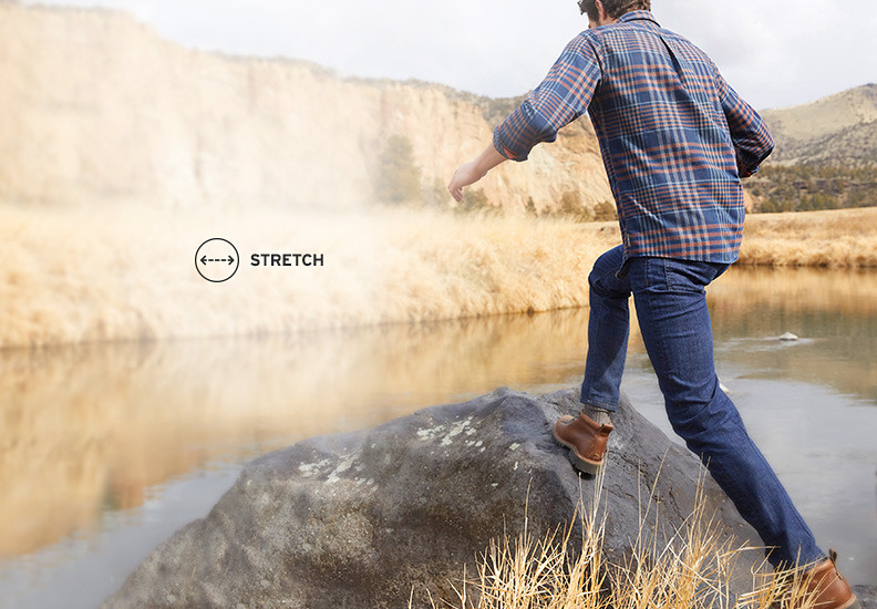 Man wearing flex jeans stepping up onto a large boulder overlooking a lake