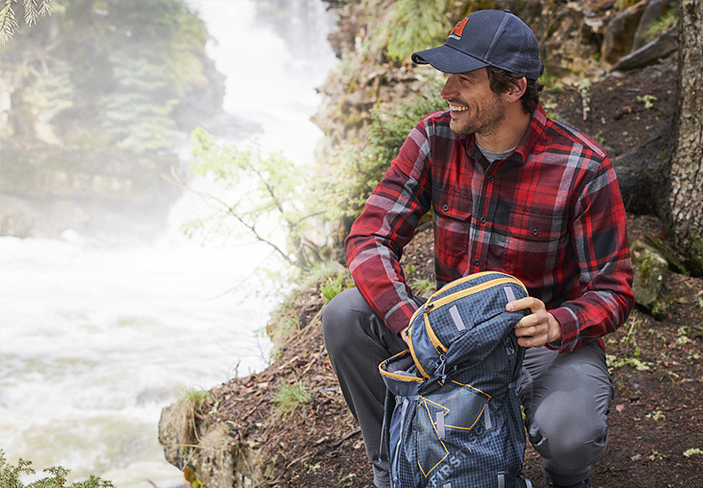 A man wearing an Expedition Performance Flannel Shirt takes a break from a hike near a river