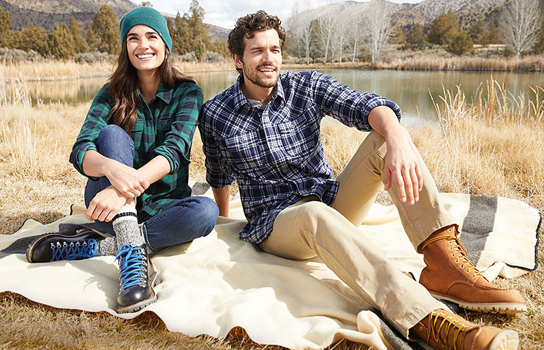 Woman and man dressed for hiking sitting on a blanket outdoors wearing K-6 Boots and K-8 Boots