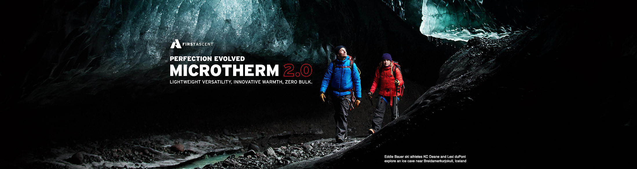 Two people wearing MicroTherm jackets walk in a dimly lit ice cave