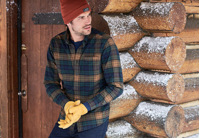 Man outside a cabin dusted with snow wearing flannel shirt with hat & gloves