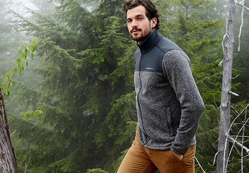 Man walking with hands in pockets through green forest in brisk temperatures wearing Radiator Pro Sweater Fleece Full-Zip Jacket