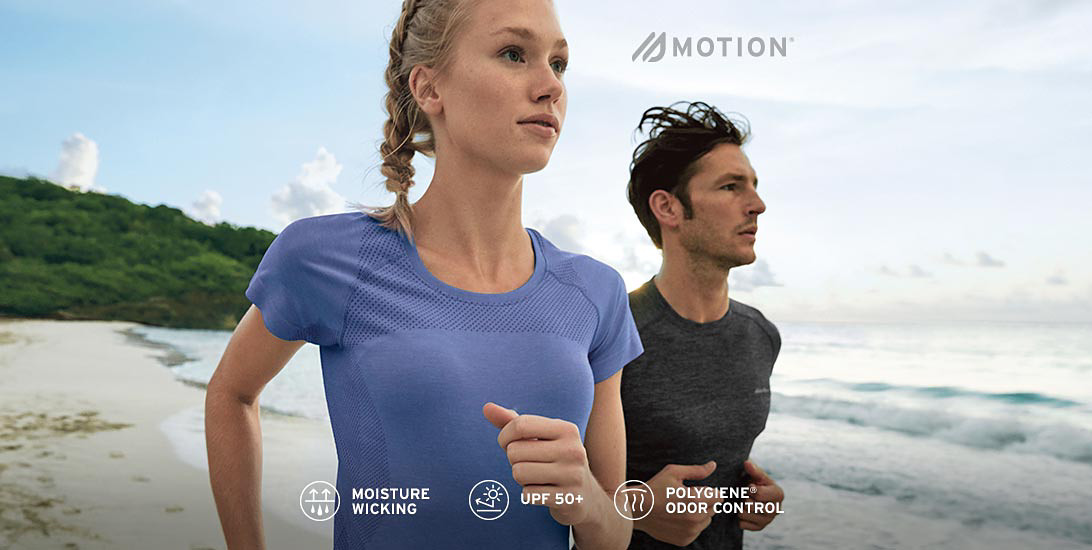 A man and a woman wearing Resolution T-shirts run on the beach