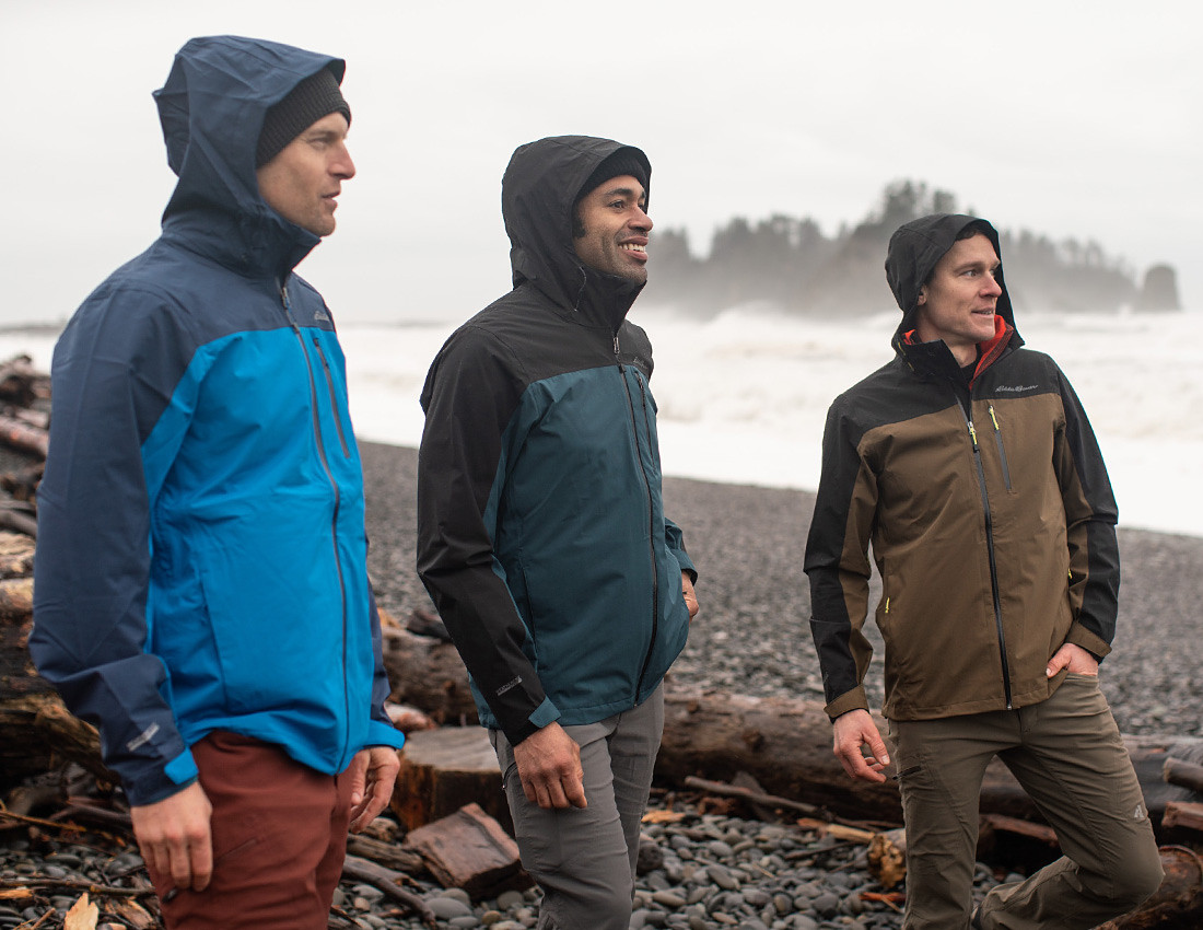 Three men on a rainy beach wearing Cloud Cap Stretch 2.0 Rain Jackets